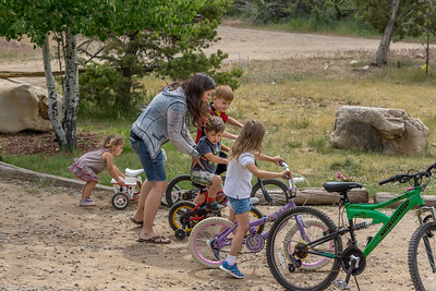 A mom steadies her son on his bike as he gets ready to race with his brother and sisters.