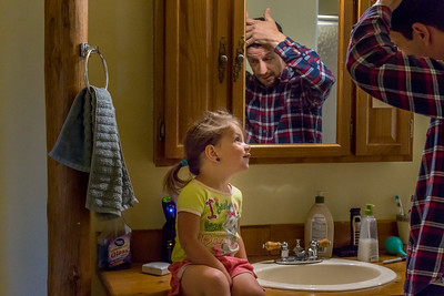 A young girl sitting on the bathroom counter talking to her father as he combs his hair.
