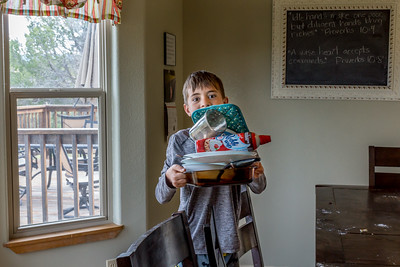A boy clears the dishes from the table after the family meal.