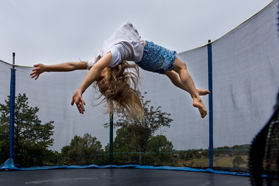 A girl in mid air as she does a back flip on a trampoline.