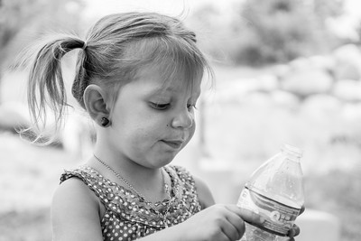 Black and white portrait of young girl examining the label of her water bottle.