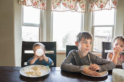 Three children sitting at a table waiting to eat.