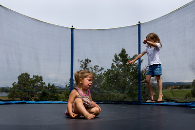 A young girl sits in the middle of a trampoline crying and her older sister gets ready to do a flip behind her.