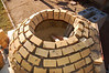 The teardrop shape has mostly been corrected.  Now the hole is just mildly egg-shaped.  Tricky, slow going at this stage.  Each course requires fewer bricks, but I needed almost four hours to complete the two courses I did today.