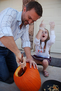 Carving the pumpkin with Daddy.  Pumpkin seeds went flying!