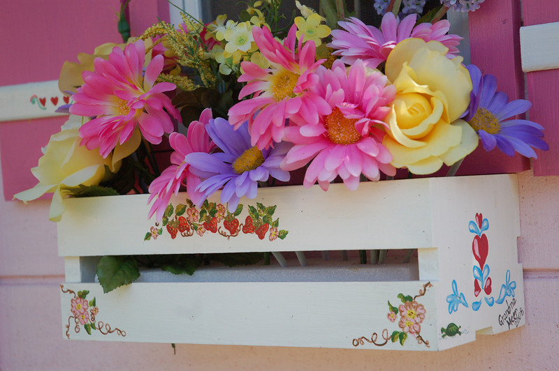 My mother tole painted the flower boxes and decorative pieces on the shutters.  The sides are done in Swedish rosemaling style as a nod to Ainsley's Swedish heritage on her father's side.  Grandma also hid a different tiny animal on each window box.  Ainsley chose the flowers.