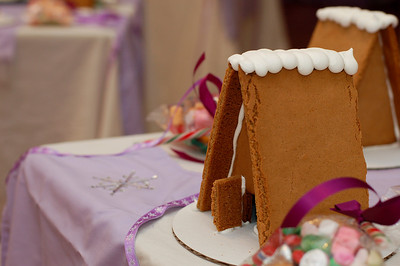 On each table, there was a gingerbread house, bag of candy, bag of icing, and apron for each girl.