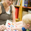 reading to toddlers - a pregnant mother reads to her one year old son