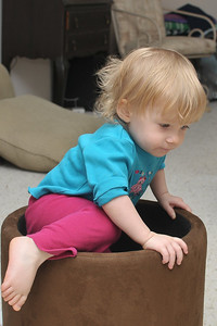 Ella loves playing in the footstool