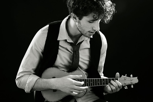 Portrait of a young man playing a ukelele