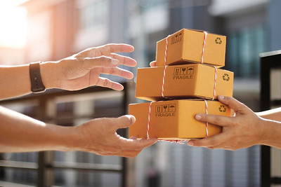 Hands of customer receiving a cardboard boxes parcel from delivery man in the morning, delivery service concept