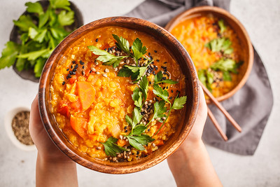 Yellow Indian vegan lentil soup curry with parsley and sesame in a wooden bowl in hands.