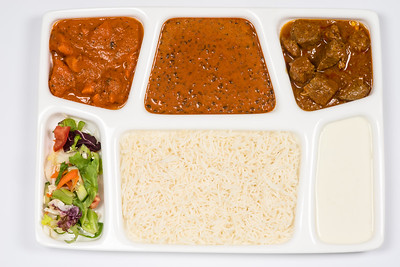 Traditional Indian meal chicken and/or lamb thali with dal makhani, chana masala, salad and basmati rice on white thali plate isolated from background