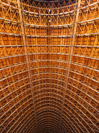 Looking up ward into the enormous redwood vaulted roof in hangar 2. Built during WWII, steel was in short supply for war so the building is built from locally abundant redwood and concrete.