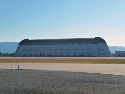 The enormous and historic Hangar 1 at Moffett Field, built in 1933. The floor covers 8 acres and can accommodate 10 football fields. The airship hangar  measures 1,133 feet long and 308 feet wide. The walls curve upward and inward, to form an elongated dome 198 feet (60 m) high.