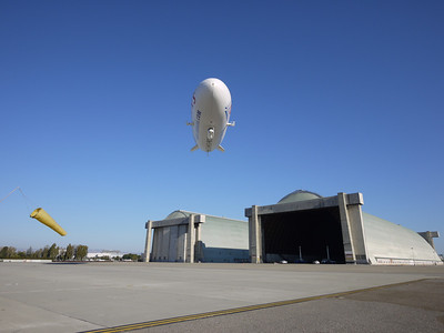 The Airship Ventures Zeppelin landing at Moffett Field in front of airship hangars 2 and 3.