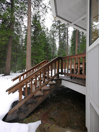 Back deck stairs toward the garage side of the house. Under the snow is a concrete pad.