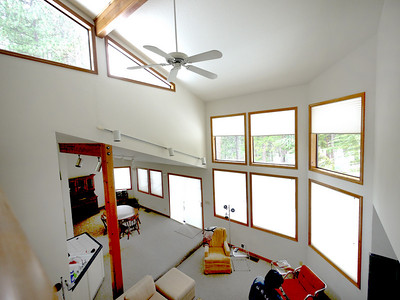 Living room and dining room from the mezzanine, showing the tall ceiling and clerestory windows