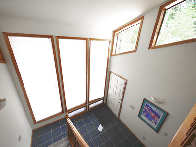 Looking down at the tall windows and blue tile of the foyer