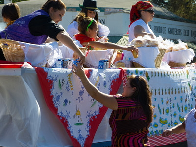 """Handing out bread and milk to the crowd at the annual Portuguese """"Our Lady of Fatima"""" Celebration parade in Thorton, CA."""