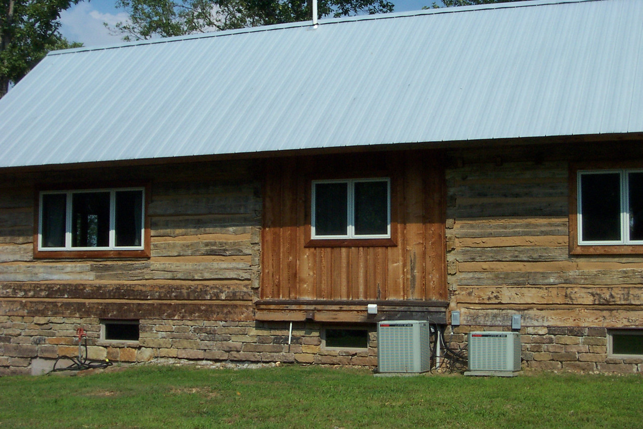 "This is the backside of the cabin.  It was originally built in Kentucky, and it once had an open ""dog run"" in the middle.  You can see in this shot that they filled in the open space.  And note the air conditioner units--thank goodness for those!"