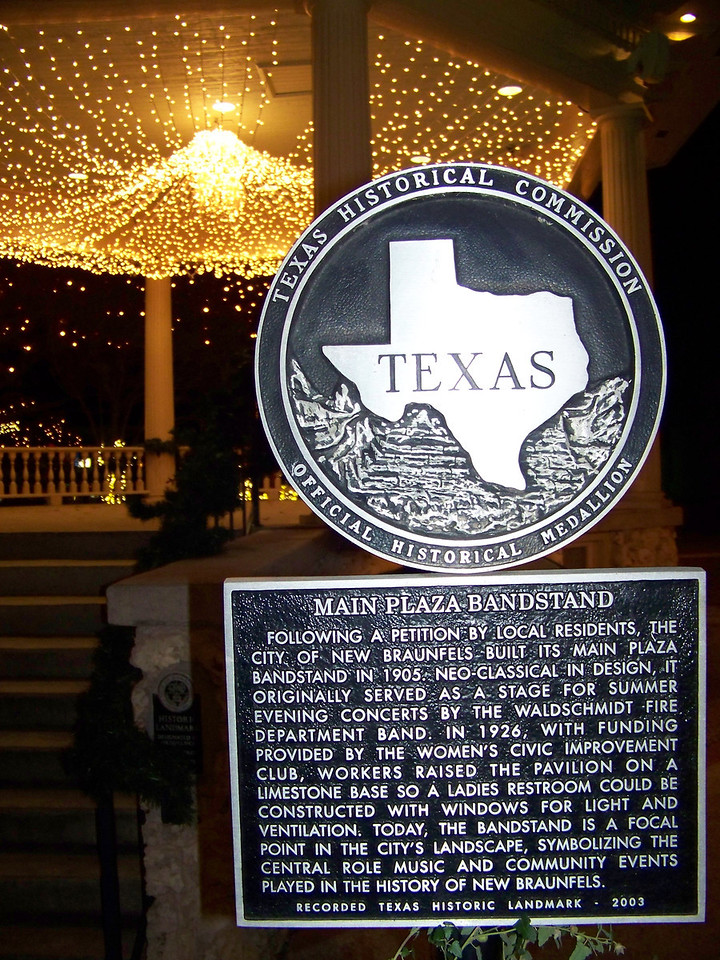"In 2003, the bandstand received a historical marker, which reads:  ""Following a petition by local residents, the City of New Braunfels built its Main Plaza bandstand in 1905.  Neo-Classical in design, it originally served as a stage for summer evening concerts by the Waldschmidt Fire Department Band.  In 1926, with funding provided by the Women's Civic Improvement Club, workers raised the pavilion on a limestone base so a ladies restroom could be constructed [in the base] with windows for light and ventilation.  Today, the bandstand is a focal point in the city's landscape, symbolizing the central role music and community events played in the history of New Braunfels."""