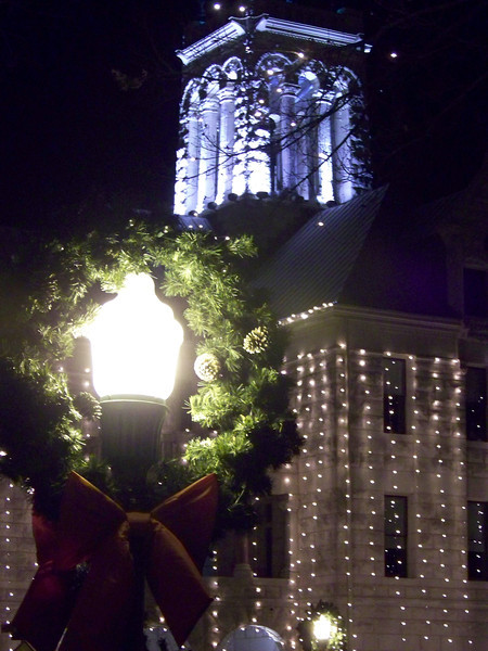 A lamp post on the Plaza decorated with a wreath, with the Comal County Courthouse in the background.