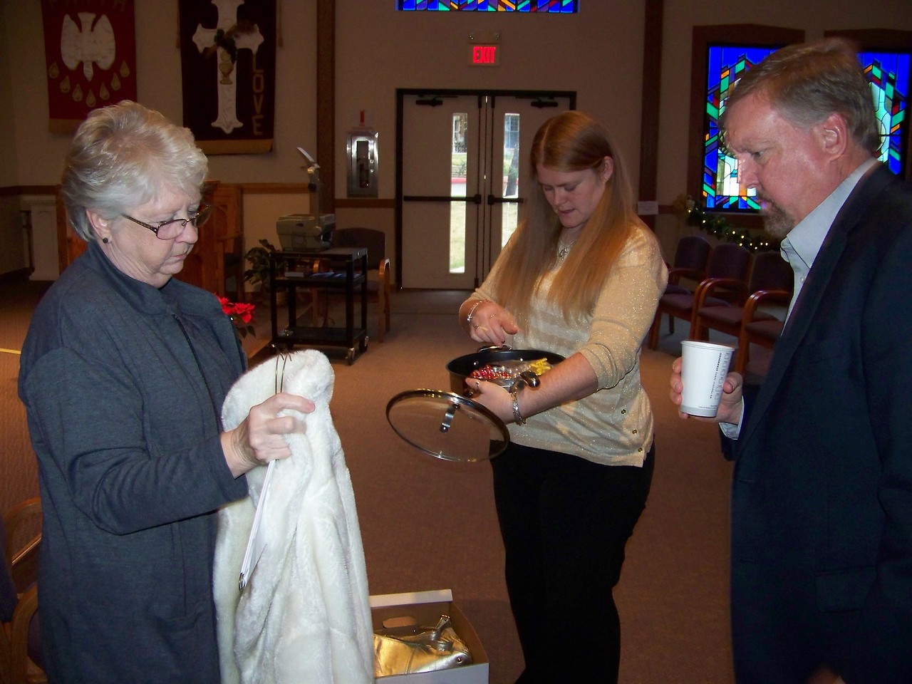 Sheri (at left, with Jenna and Mark) handled the lion's share of the arrangements for Aunt Pet's memorial.  They were setting up some of her signature belongings for the service.