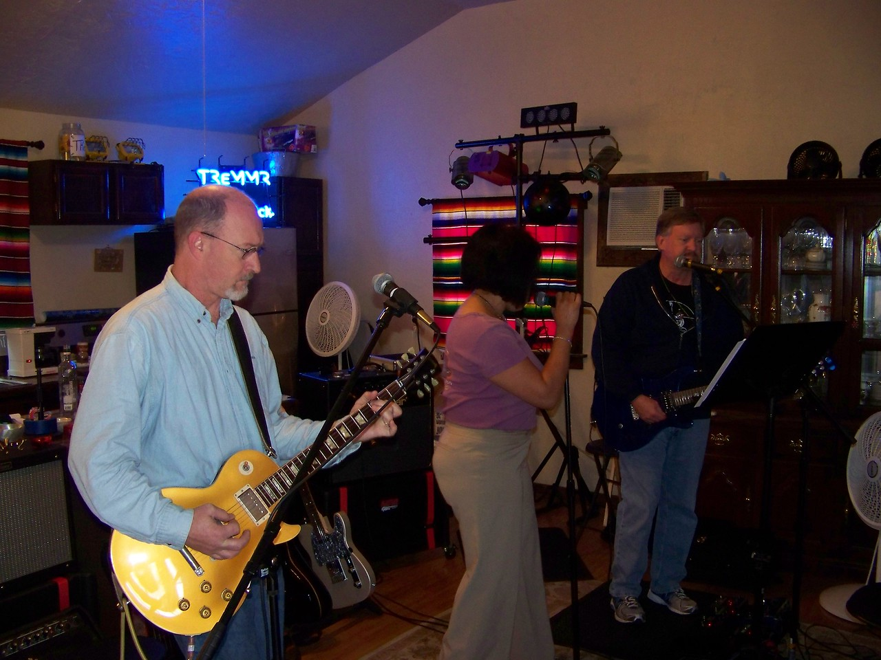 Mike (at left) plays rhythm guitar.  The band was practicing in his guest house, which makes a really great rehearsal space.  You can see Mike's neon sign right behind him.