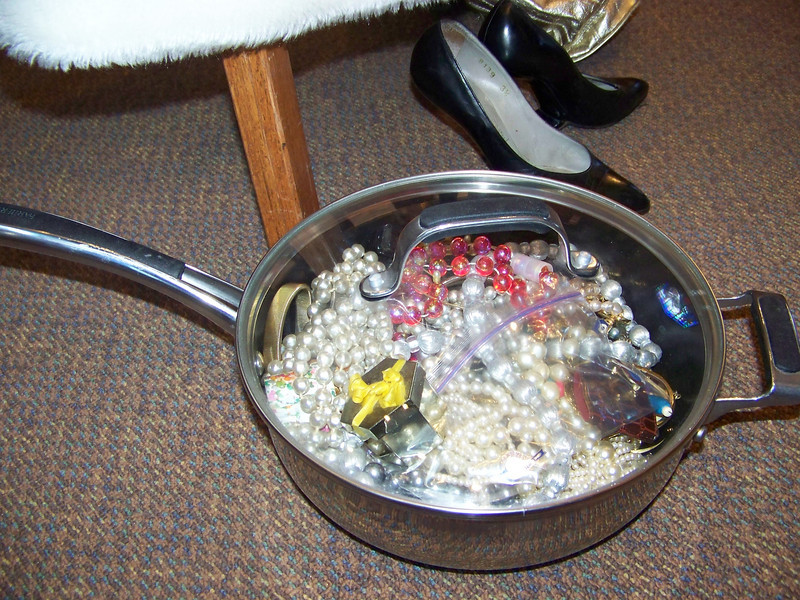 "Aunt Pet was rather eccentric.  She loved garage sales, and had picked up quite an unusual collection of items over the years.  When Sheri was going through her belongings, she found this large frying pan filled with Mardi Gras-type beads and other costume jewelry.  We're not sure if Aunt Pet ever actually wore any of the jewelry or even used the frying pan.  Sheri decided to bring it ""as-is"" to the service to represent that bargain-hunting collector side of her personality."