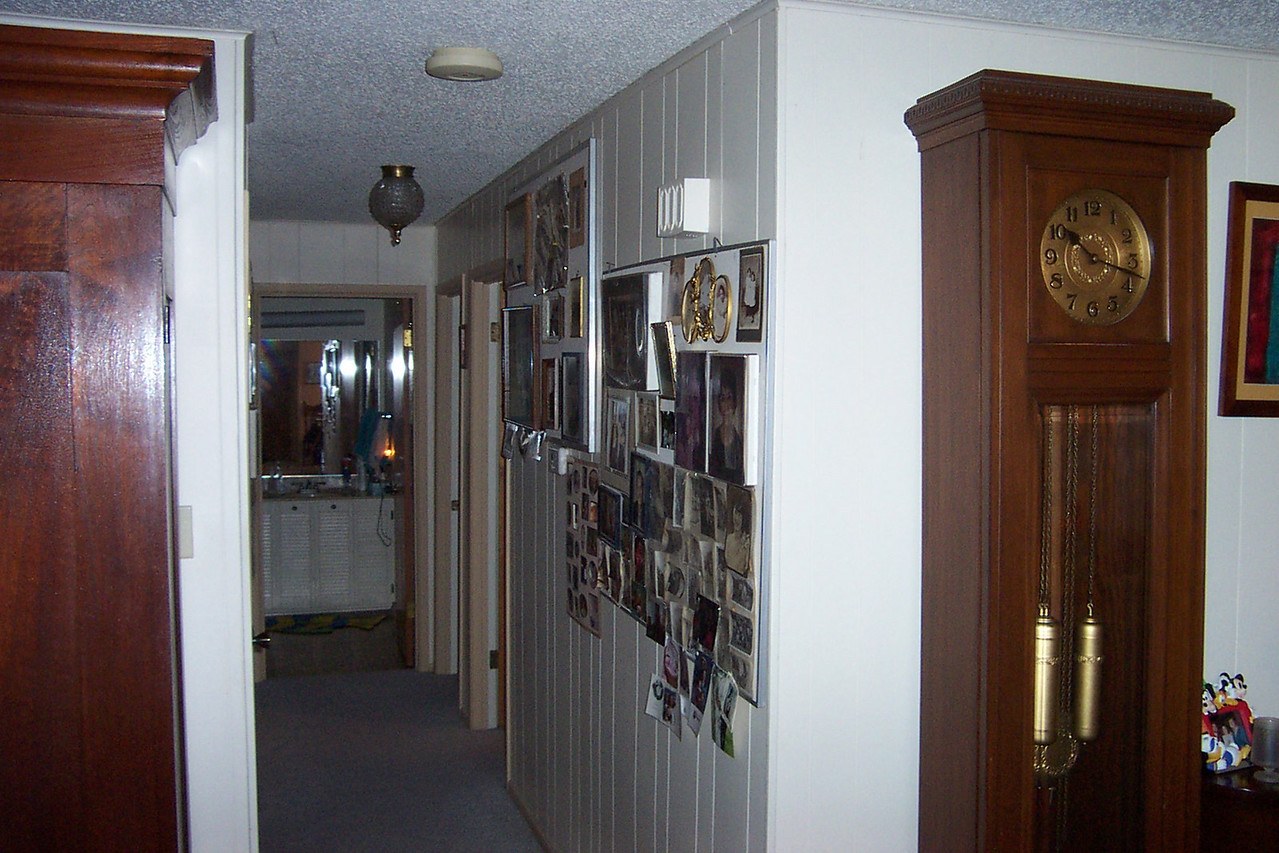 Coming off the living/dining room is a hallway that Mom has covered in family photos.  There are two small bedrooms to the right, and the master bedroom is to the left.  At the end of the hall is one of the bathrooms.