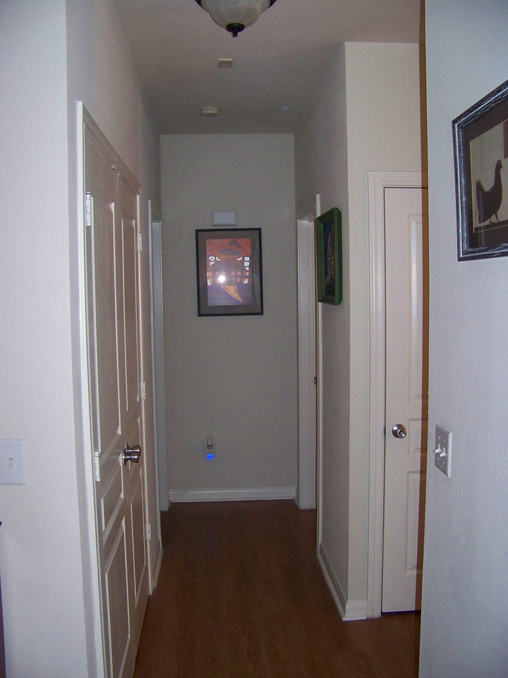Hallway with the kitchen to the right.  On the left is a closet with the washer & dryer.  Further down the hall, the bedroom is to the right and the bathroom is to the left.