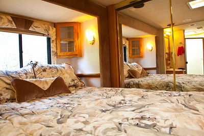 National RV Sea Breeze 5th wheel. View of bedroom queen bed, corner cabinets, day/night shades, accent lighting, full-width mirrored closet.