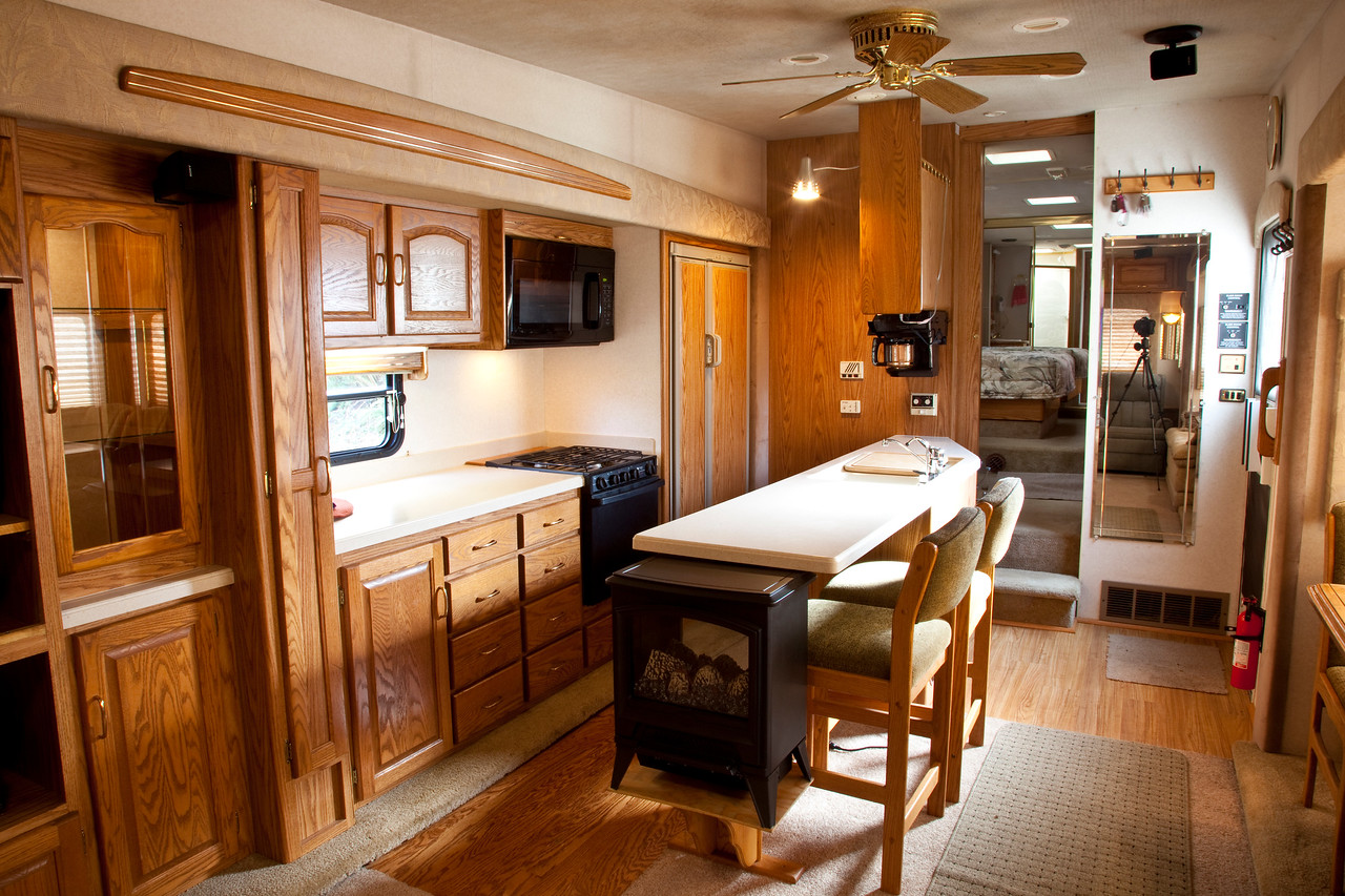 National RV Sea Breeze 5th wheel. View of kitchen island, side by side refrigerator/freezer with coffee maker, oak floor, oak face cabinets, bar seating, composite counter tops, porcelian sinks, three burner stove, oven, full-size microwave, ceiling fan and slide out pantry storage.