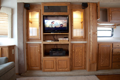 National RV Sea Breeze 5th wheel. View of entertainment center, flat screen TV, dvd player, surround sound, glass door lighted cabinets.