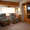 National RV Sea Breeze 5th wheel. View of main living area with two rocking recliners, entertainment center, day/night shades, accent lights, overhead storage.