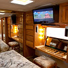 National RV Sea Breeze 5th wheel. View of bedroom dressing table with vanity lighting and mirrors, built-in flat-screen TV on swivel with mounted sound and audio. Full length mirrored closet with built in bureaus.