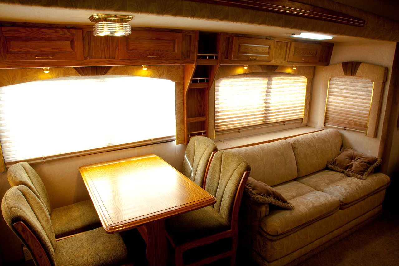 National RV Sea Breeze 5th wheel. View of main living area, dining for four, day/night shades, overhead lighting, accent lights, overhead storage and sleeper sofa.