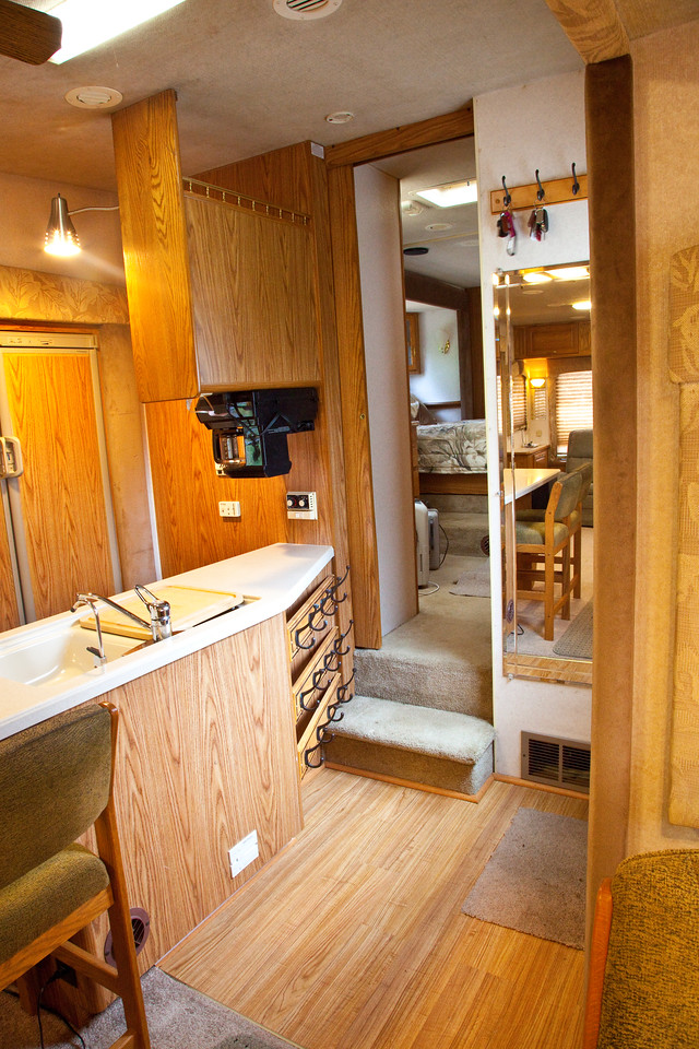 National RV Sea Breeze 5th wheel. View of main entry showing kitchen island, coffee maker, composite counters, full length mirror, forced air furnace intake, coat racks, shoe racks, entry to bedroom and bathroom area.