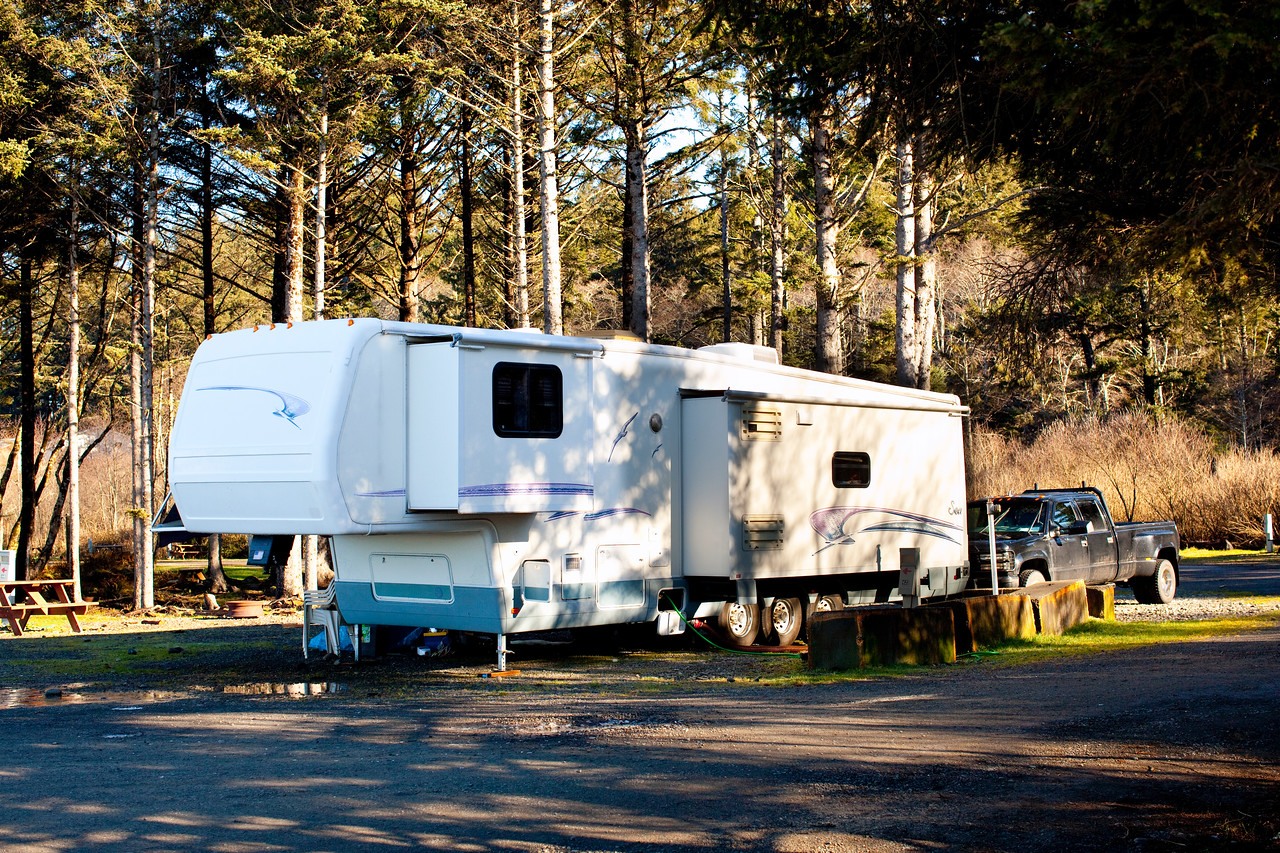 National RV Sea Breeze 5th wheel at an RV park. Bedroom and main slides extended. Notice electric leveling jacks and slide toppers.