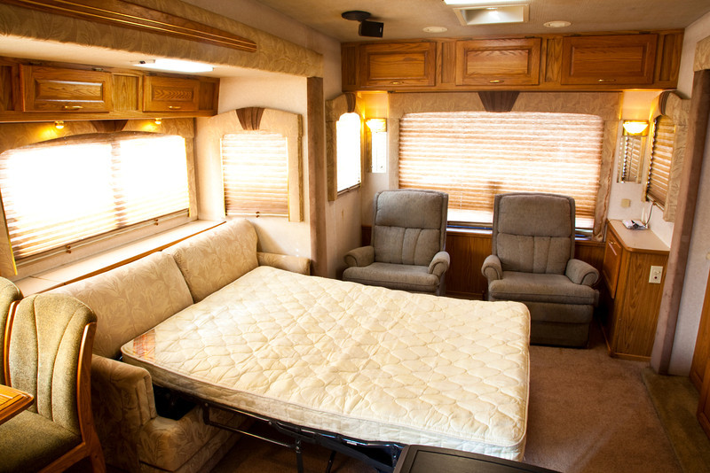 National RV Sea Breeze 5th wheel. View of main living area with two rocking recliners, day/night shades, overhead lighting, accent lights, overhead storage and sleeper sofa opened to full-size double bed.
