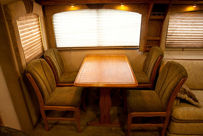 National RV Sea Breeze 5th wheel. View of main dining area for four, day/night shades, overhead lighting, accent lights, upholstered dining chairs and oak dining table.