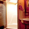 National RV Sea Breeze 5th wheel. View of tub/shower with skylight and etched glass door, vanity, sink and medicine cabinet with built-in blow-dryer.