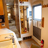 National RV Sea Breeze 5th wheel. View of main entry showing kitchen island, coffee maker, composite counters, full length mirror, forced air furnace intake, coat racks, fire extinguisher, room slide controls and entry to bedroom and bathroom area.