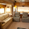 National RV Sea Breeze 5th wheel. View of main living area with two rocking recliners, day/night shades, overhead lighting, accent lights, overhead storage and sleeper sofa.