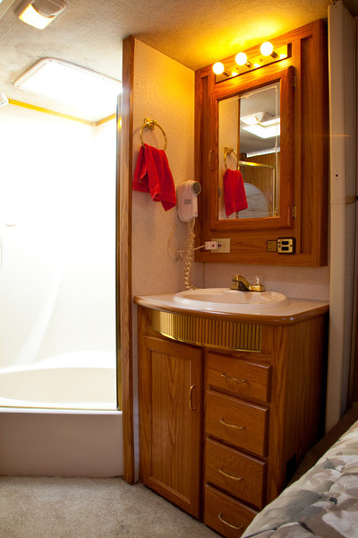 National RV Sea Breeze 5th wheel. View of tub/shower with skylight and etched glass door, vanity, sink and medicine cabinet with built-in blow-dryer and under-sink storage.