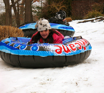 Genna tubing down the hill.