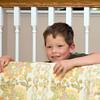 Adrik hides behind the sofa