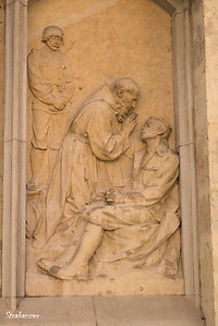 Graz, Steiermark, Austria  08/25/2017 Sculpture on the wall of the cathedral depicing a priest giving the last Rites to a dying soldier.    (cf previous picture). This work is licensed under a Creative Commons Attribution- NonCommercial 4.0 International License