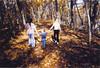 3 kids walking in woods